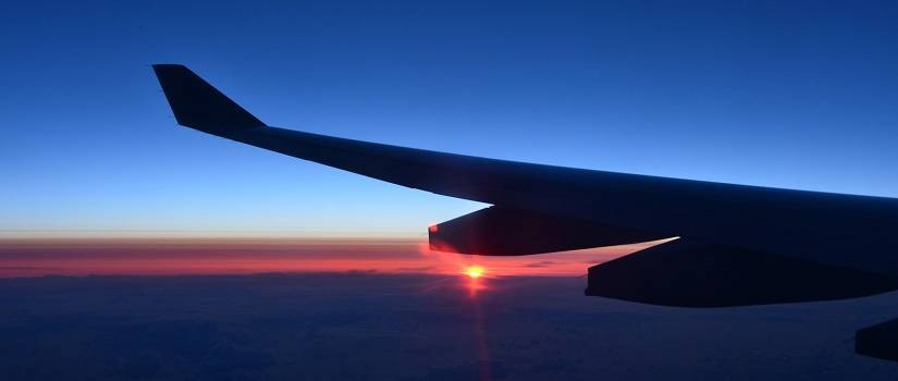 Airplane wing with sunset in the background