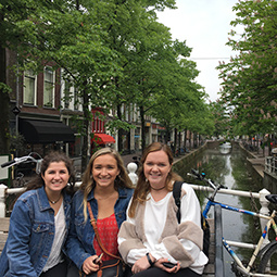 three students posing by a canal in Amsterdam
