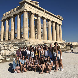 Students sitting in front of ancient ruins