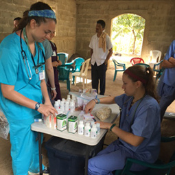 students in scrubs organizing medicine on a table