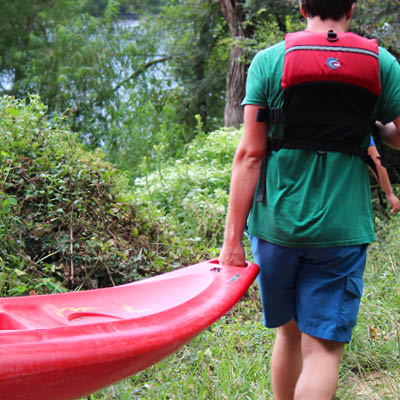 Student in a life vest carrying a red kayak.