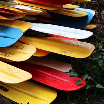 A stack of colorful canoe paddles.