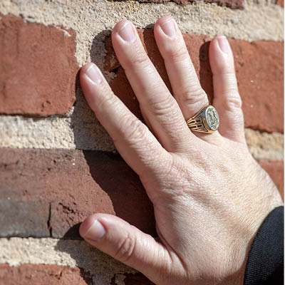 a hand with class ring touching bricks