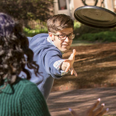 student throwing a frisbee outdoors