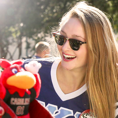 student in sunglasses outdoors smiling at a smalled Cocky toy