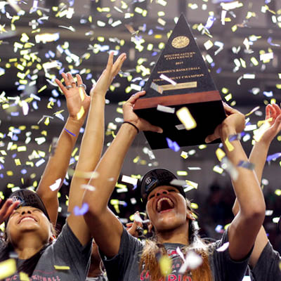 women's basketball team under confetti with trophy
