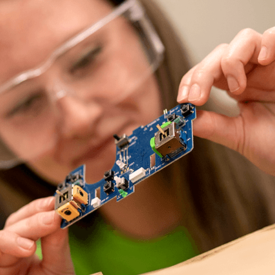 Close-up of a student holding a circuit board.