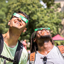 two guys looking at the sky with eclipse glasses on
