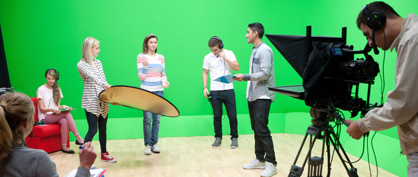 Students using lighting equipment in front of a green screen