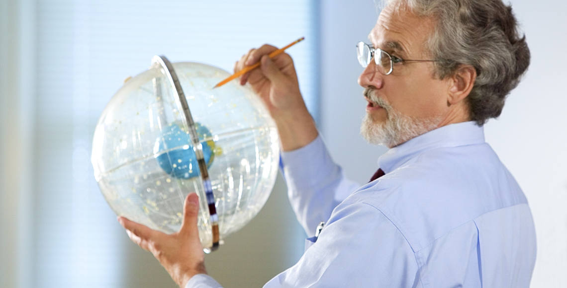 Professor holds up a clear astronomical globe of constellations with the earth inside
