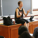 Female Professor lecturing while sitting on desk