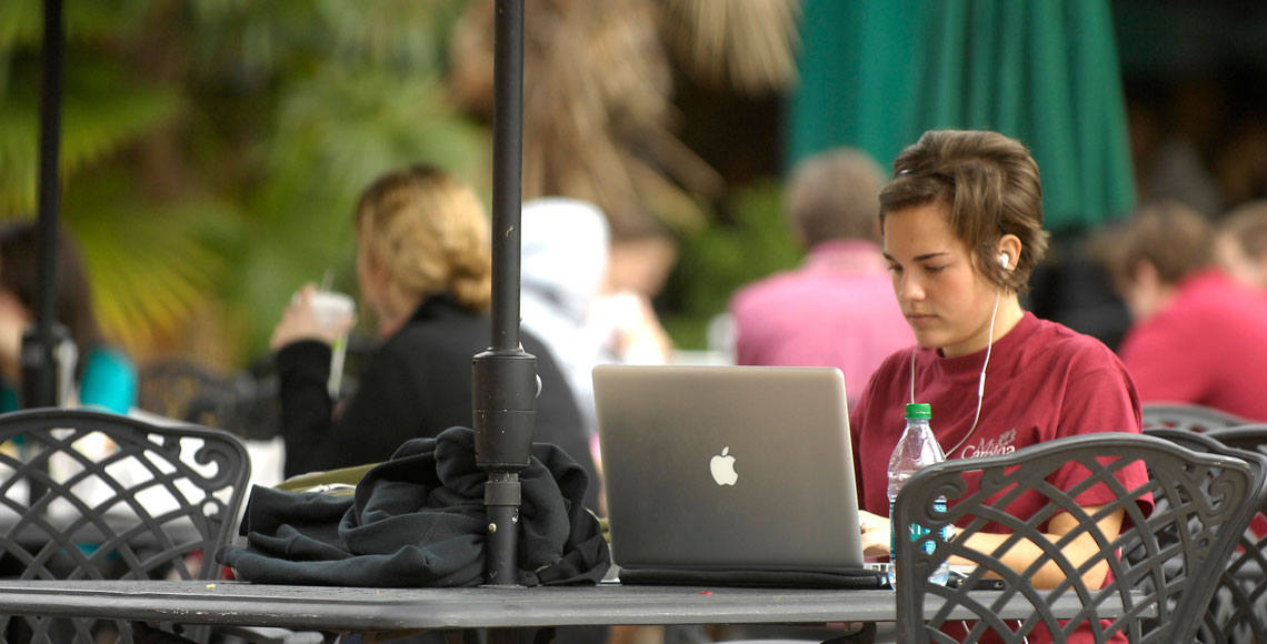 Student sitting at table using a laptop