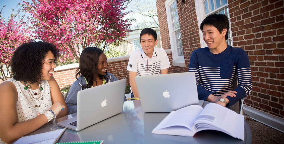Students sitting at table outside with books and computers
