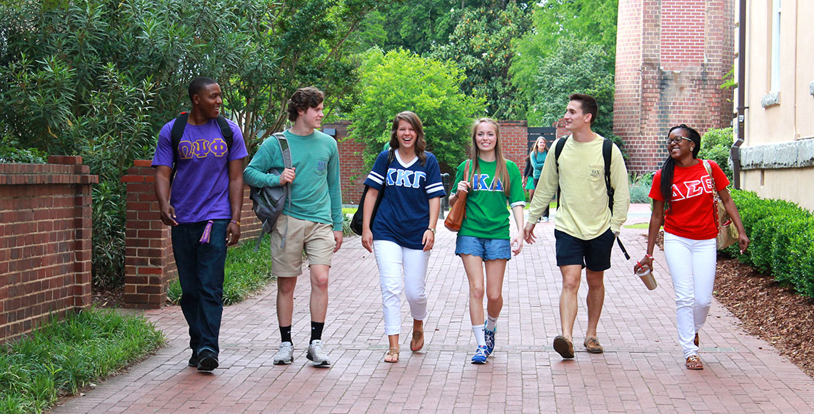 students in greek letter shirts walking across campus
