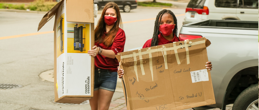 Resident Mentors assist guest by carrying two large boxes during Move-In
