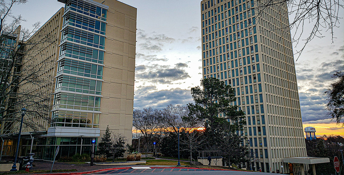 Sun rising behind Patterson Hall and South Tower