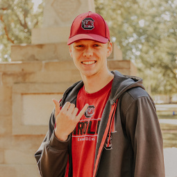 Male student standing next to the Maxcy monument giving the spurs up hand gesture