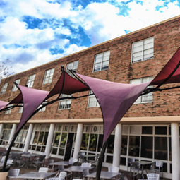 Garnet outdoor screen coverings in the foreground of Mcbryde residence hall.