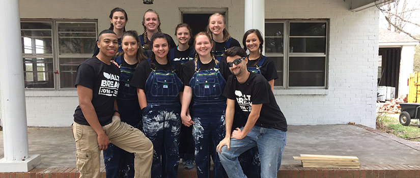 A group of students show off their paint covered overalls after a long day of work during an Alt Break trip.