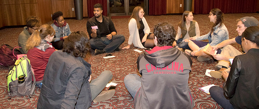 Students sit on the ground in a circle and discuss topics related to hunger and homelessness.