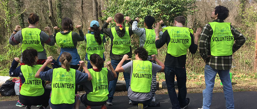 Volunteers show-off their reflective vests during a clean-up day.