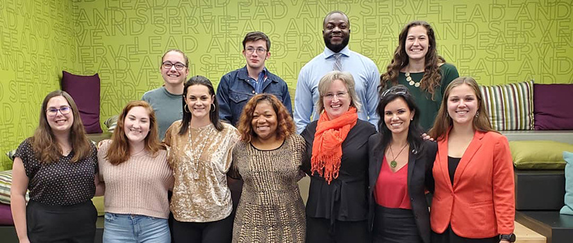 leaders pose with a bright green background behind them. The location is the leadership and service center in Russell House.