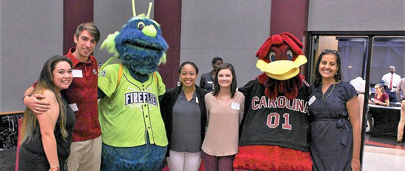 Students pose with Cocky and the Columbia Fireflies mascot.