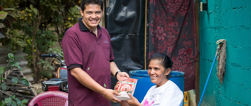 A Nicaraguan man and woman hold a book and smile.