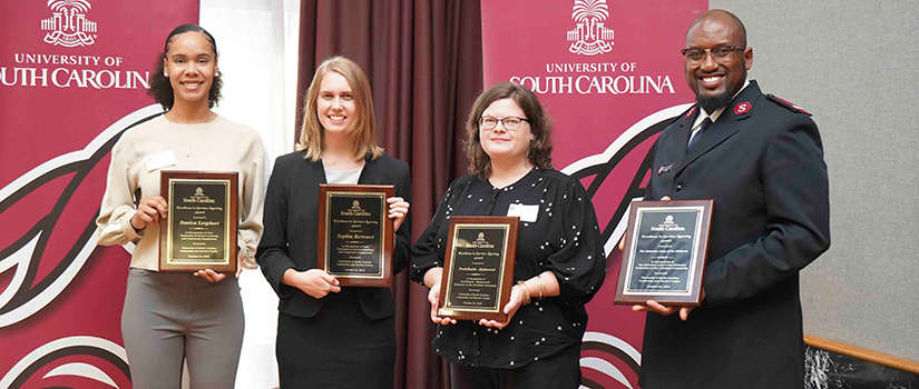 award winners pose in front of a UofSC banners. They hold their awards in their hands.