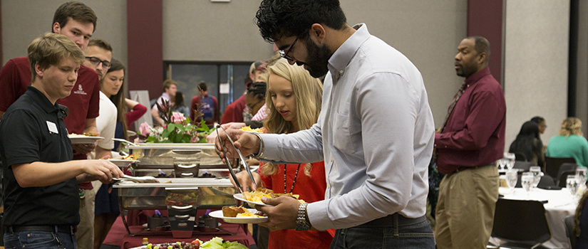 Students fill their plates at the TOAST breakfast awards buffet.