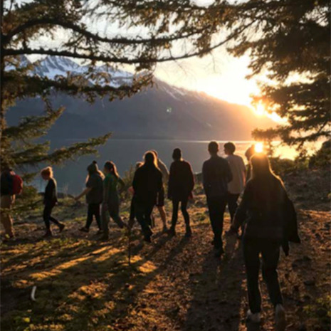 Students hike on mountain during golden hour. The mountain and a body of water are seen in the background.