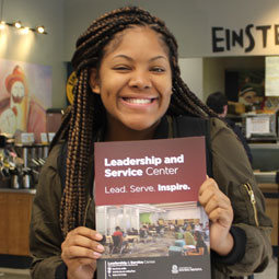 A student proudly displays a Leadership and Service Center brochure.