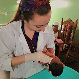 A student holds a baby during clinical work on a service mission trip.