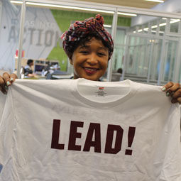A student displays a T-shirt printed with LEAD.