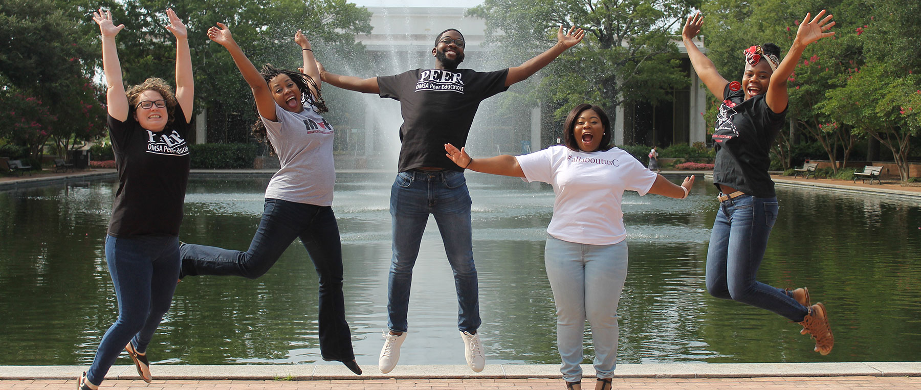 The OMSA team jumps for joy in front of the Thomas Cooper Library fountain.