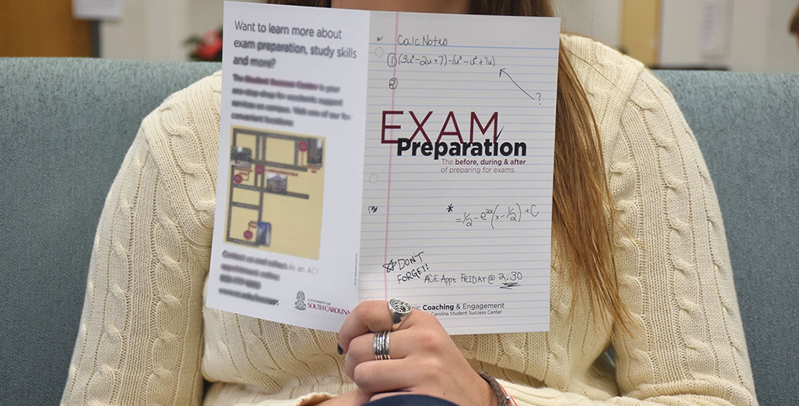 Student holds up an exam preparation booklet