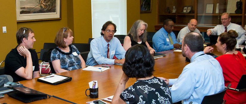 Faculty and staff members gather at a round table for a discussion