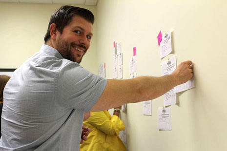 A smiling man places sticky note on a wall of sticky notes