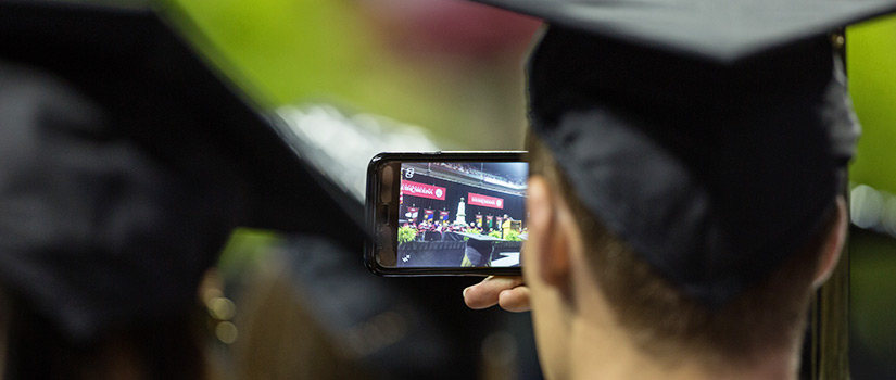 student with camera phone at graduation