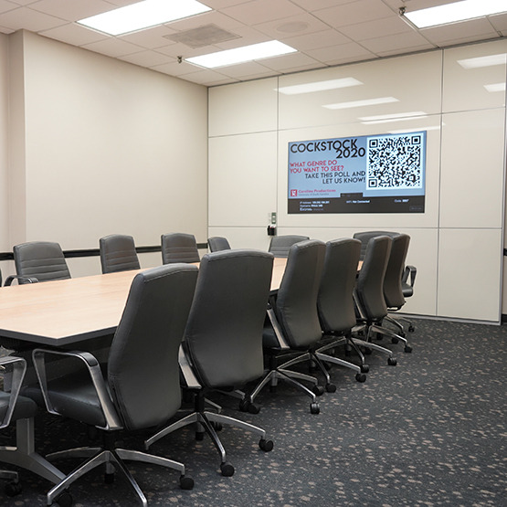 conference table with chairs and a board on the wall with paper to write on