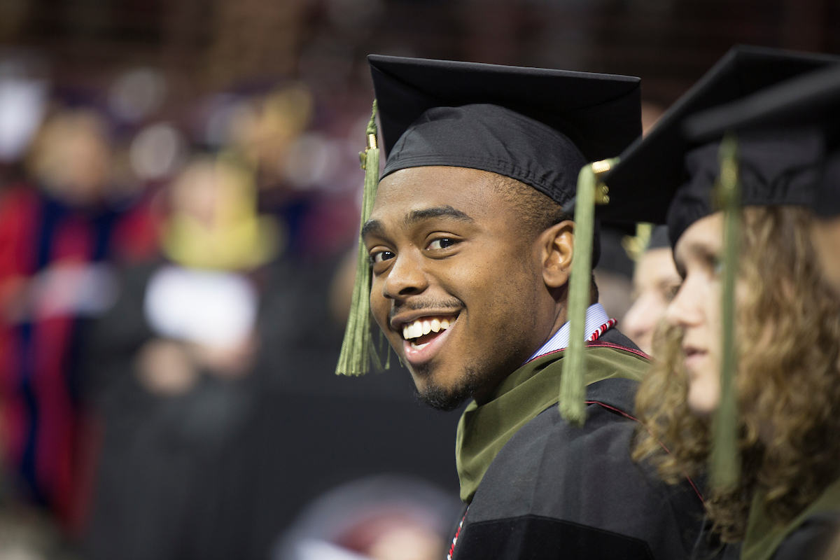 a Carolina graduate smiles at a commencement ceremony