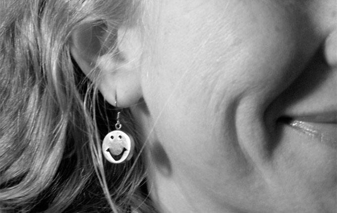 A hearing-impaired student captures a self portrait, displaying only her dimpled cheek and her ear, which is adorned with a smiley-faced earring.
