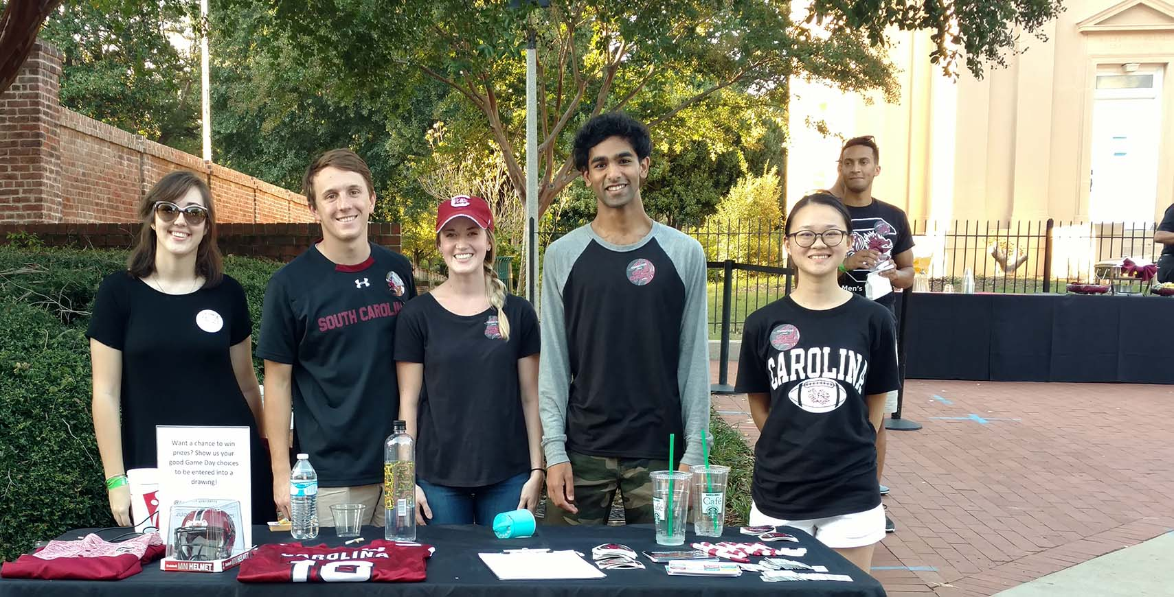 USC students stand behind a merchandise table on Greene Street, smiling