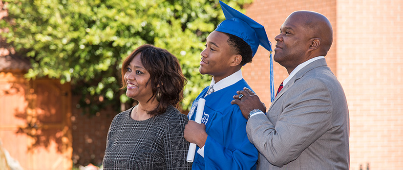 A male student in his graduation cap and gown posing for a photo with his parents.