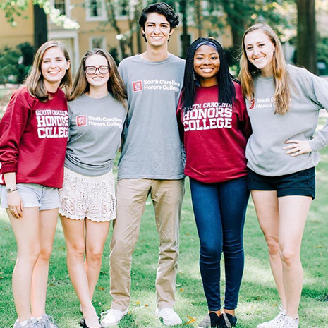 Group of honors college students standing on the horseshoe wearing honors college shirts and hats