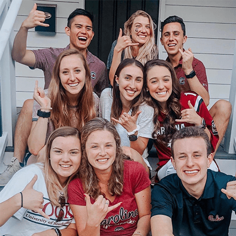 A group of students gathered on porch steps in garnet and black