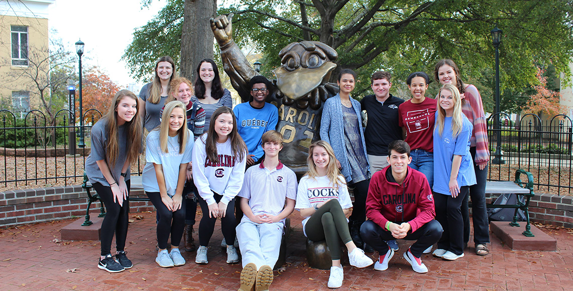 A University 101 class posing in front of the Cocky statue.