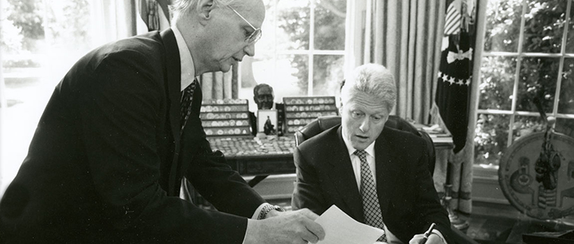 Governor Riley and President Bill Clinton examine a document in the Oval Office. Riley is leaning over desk, holding a paper. Clinton is seated.