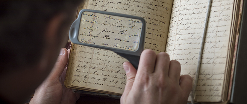 person reading a handwritten journal with a magnifying glass