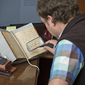 Over the shoulder view of a person using a handheld magnifying glass to read handwritten text in a manuscript. The book is resting in a book cradle on the table.